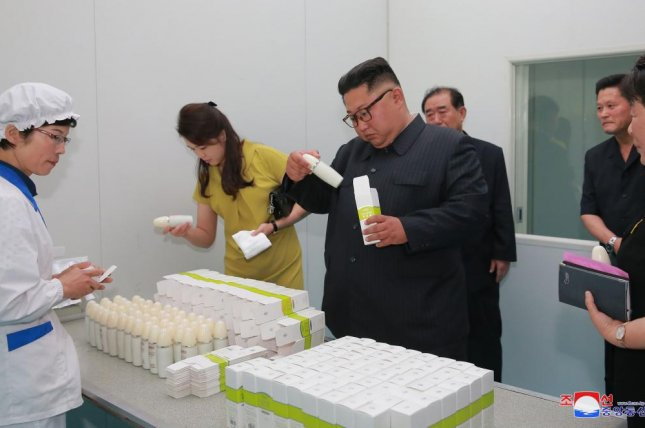 A photo released by the official North Korean Central News Agency shows North Korean leader Kim Jong Un (C) and his wife, Ri Sol Ju, second from left, inspecting products at Bom Hyang Gi cosmetics factory in 2018. File Photo by KCNA