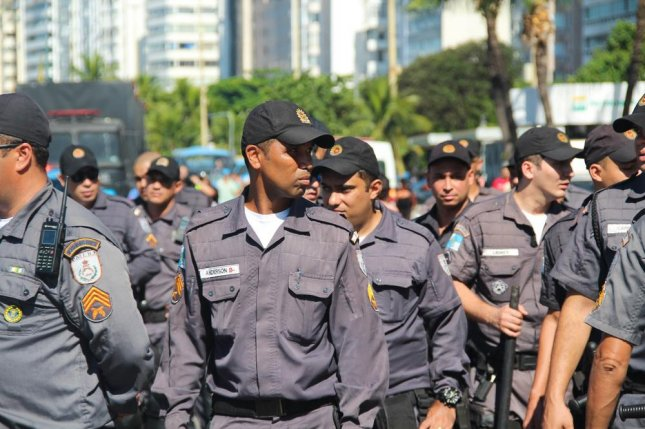 Police appear during protests on April 17 in Brazil against Dilma Roussef's impeachment in Copacabana Beach in Rio de Janeiro. One month before the Summer Olympics, some police officers in Rio, who claim they haven't been paid in weeks, posted a sign outside Rio's main airport that says: Welcome to Hell. Police and firefighters don't get paid, whoever comes to Rio de Janeiro will not be safe. Photo by Andre Luiz Moreira/Shutterstock