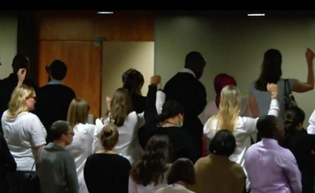 United Nations staff members protested the announcement of Wonder Woman as an honorary ambassador with backs turned and fists raised during a ceremony on Friday. Wonder Woman was named Honorary Ambassador for the Empowerment of Women and Girls as part of a campaign to raise awareness on Sustainable Development Goal 5, achieving gender equality and empowerment for all women and girls. Screen capture/ITN/AOL