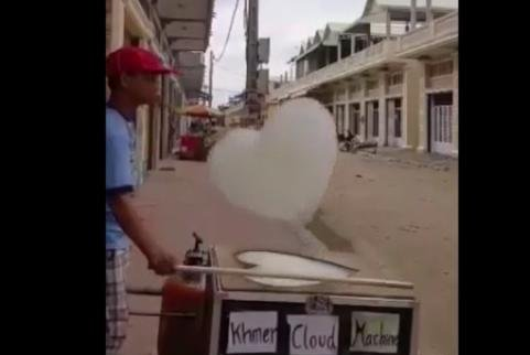 A machine makes heart-shaped clouds out of foam on a Cambodian street. Screenshot: Storyful