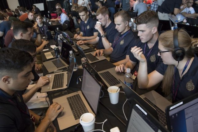A team of Naval Midshipmen and Air Force Airmen from the Naval Academy and Air Force Academy participate in rack one during HacktheMachine competition at the Brooklyn Navy Yard in New York City in September 2019. Photo by Bryan lyankoff/U.S. Navy