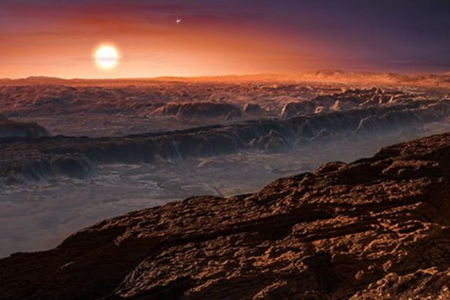 An artistic rendering imagines what the surface of the exoplanet Proxima b might look like. The planet's sun, the red dwarf star Proxima Centauri seen just above the horizon, is the closest star to our own solar system. Photo by ESO/M. Kornmesser