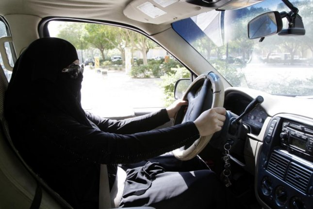 A Saudi woman sits behind the wheel of a car in Riyadh, Saudi Arabia, in 2013. King Salman issued a decree Tuesday, saying that by next June, women in his nation would be able to legally drive. File Photo courtesy EPA-EFE/STR