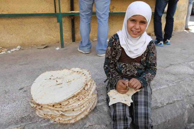 With many men gone -- or afraid to leave home -- children in Damascus are being sent out to earn money or do the household errands. Here a girl sells tortillas on the street. Photo by ART production/Shutterstock