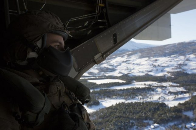 U.S. Marine Corps Cpl. Hayden F. Smith, with Marine Medium Tiltrotor Squadron 365, observes the landscape from a MV-22 Osprey during Exercise Trident Juncture 18 near Vaernes Air Station, Norway, in 2018. Photo by Camila Melendez/U.S. Marine Corps