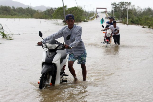 Filipino motorists wade on a flooded road in the typhoon-hit town of Casiguran, Aurora province, Philippines, on Tuesday. Photo by Nel Maribojoc?EPA