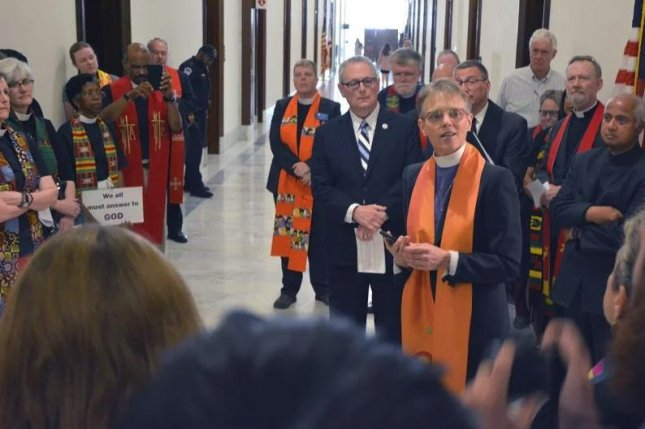 Episcopal Bishop Mariann Budde of Washington, D.C., speaks to a crowd protesting outside Sen. Mitch McConnell's office in Washington on Tuesday. Photo by Jack Jenkins/RNS