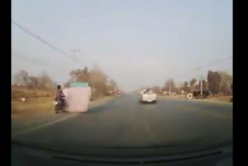 A motorcyclist collides with a mattress that fell from a pickup truck in Thailand. Screenshot: Vijit Sooksai/Facebook