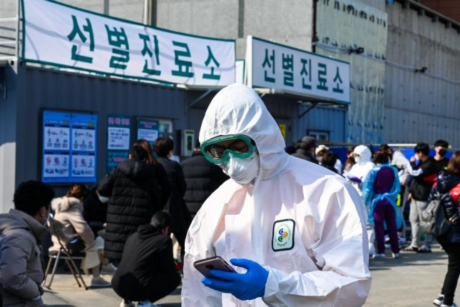 A hospital worker in a biohazard suit works at a makeshift reception area to receive potential COVID-19 patients at Daegu Medical Center in South Korea on Friday. Photo by Thomas Maresca/UPI