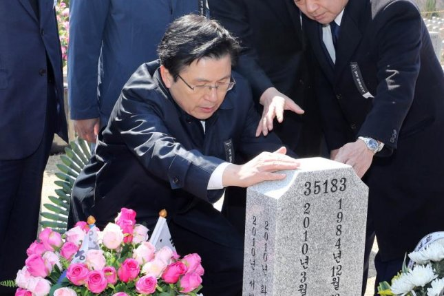 Hwang Kyo-ahn (C), chief of the main opposition Liberty Korea Party, visits a tomb of a victim of the 2010 sinking of the Cheonan warship at South Korea's national cemetery in the central city of Daejeon on Friday. EPA-EFE/YONHAP