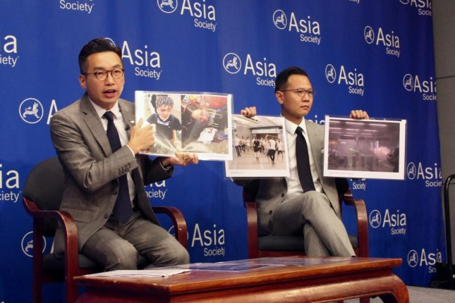 Alvin Yeung (L) and Dennis Kwok (R) hold up photos of protesters who were the targets of police brutality in Hong Kong during a discussion at the Asia Society in New York on Thursday. Photo by Elizabeth Shim/UPI