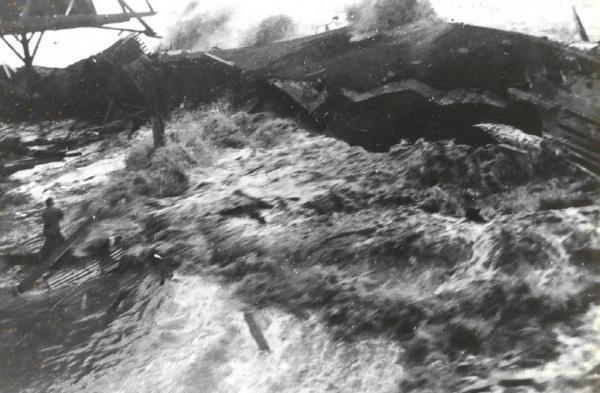 This image shows the tsunami, a result of the 1946 Aleutian Islands earthquake, coming ashore at Hilo, Hawaii on April 1, 1946. Note the man standing on the pier. This disaster provided the impetus for the establishment of the Pacific Tsunami Warning Center in Ewa Beach, Hawaii. File Photo by NOAA