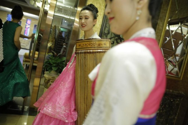 North Korean waitresses preparing to perform for guests at a Beijing-based North Korean restaurant. A group that fled from a different establishment in China are at risk of forcible repatriation, activists and defectors say. File Photo by Wu Hong/EPA