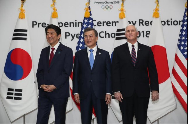 South Korean President Moon Jae-in (C) poses with U.S. Vice President Mike Pence (R) and Japanese Prime Minister Shinzo Abe during a reception to mark the opening of the 2018 PyeongChang Winter Olympics in the host town of PyeongChang on Friday. Photo by Yonhap