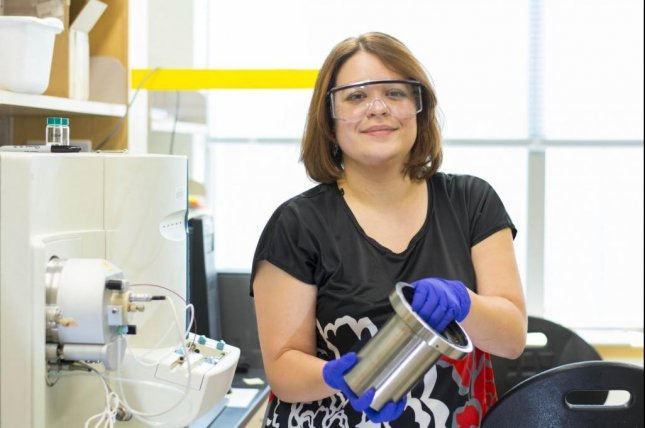WPI professor Marion Emmert holds a motor from an electric car. Photo by WPI