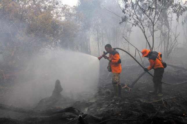 Indonesian firefighters spray water to extinguish fire in Kampar, Riau province, Indonesia, on Tuesday. Photo by EPA-EFE