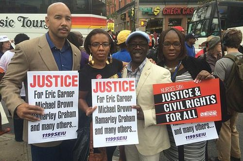 Protesters hold signs demanding justice for the death of Eric Garner. (CC/Rubin Diaz Jr.)