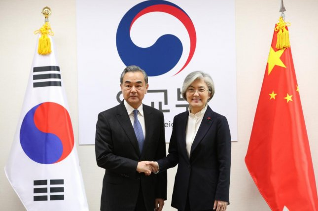 South Korean Foreign Minister Kang Kyung-wha (R) shakes hands with Chinese Foreign Minister Wang Yi (L) during their meeting at the foreign ministry in Seoul on Wednesday. Photo by Yonhap/EPA-EFE