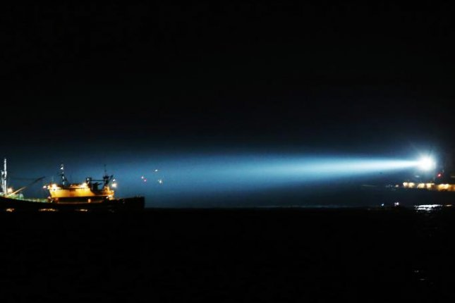A Korea Coast Guard ship (L) illuminates a Chinese fishing boat stopped for allegedly illegally operating in South Korea's territorial waters off Gageo Island in the Yellow Sea on Jan. 15, 2013. EPA