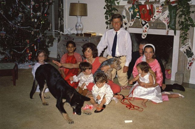 President John F. Kennedy celebrates Christmas on December 25, 1962, with his family in Palm Beach, Fla. Left to right: Caroline Kennedy; Gustavo Paredes; first lady Jacqueline Kennedy, holding her nephew Anthony Radziwill; John F. Kennedy, Jr.; President John F. Kennedy; Prince Stanislaus Radziwill of Poland (partially hidden); and Princess Lee Radziwill, holding her daughter Anna. Also pictured are the Kennedy family dogs, Clipper (left) and Charlie (held by Mrs. Kennedy). Photo courtesy John F. Kennedy Presidential Library