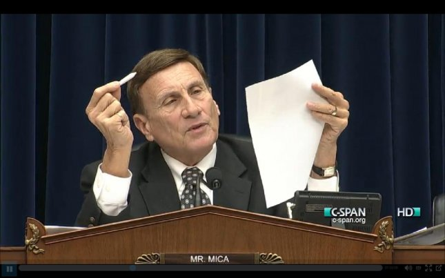 Rep. John Mica, R-Fla., holds up a fake marijuana joint and a list of the 26 federal agencies with authority in D.C. at a House Oversight Committee subcommittee hearing on May 9, 2014. (C-SPAN)