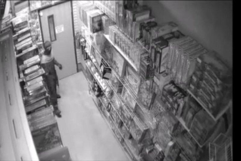 A burglar dressed in a ninja costume steals a katana sword from an Anchorage comic book store. Screenshot: John Bosco/YouTube
