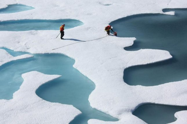 Scientists sample meltwater among the Arctic sea ice. Photo by NASA/Goddard Space Flight Center
