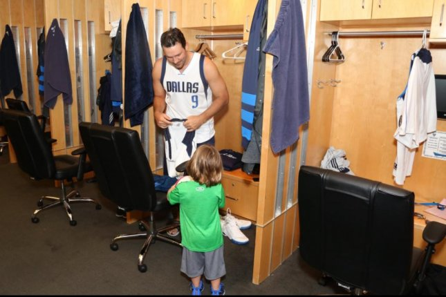 Former Dallas Cowboys quarterback Tony Romo talks to his son in the Dallas Mavericks' locker room before he suited up during a Marverick for a Day ceremony Tuesday at the American Airlines Center. (Dallas Mavericks/Twitter)