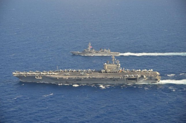 The USS Ronald Reagan (left) sails with a Japanese destroyer Tuesday in the South China Sea. Photo courtesy Japan Maritime Self-Defense Force