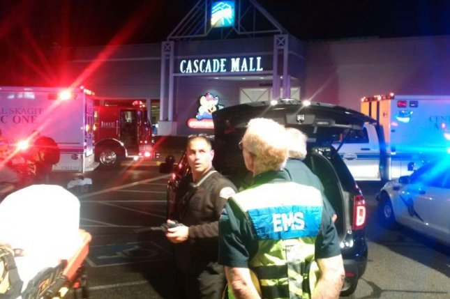 Police officers and emergency medical personnel stand outside the Cascade Mall in Burlington, Wash., on Friday night after a gunman shot at least five people inside the shopping center and fled on foot. The suspect, a Hispanic male wearing a black T-shirt, was last seen walking away from the scene toward Interstate 5. Burlington is 65 miles north of Seattle. Photo courtesy Sgt. Mark Francis/Washington State Patrol