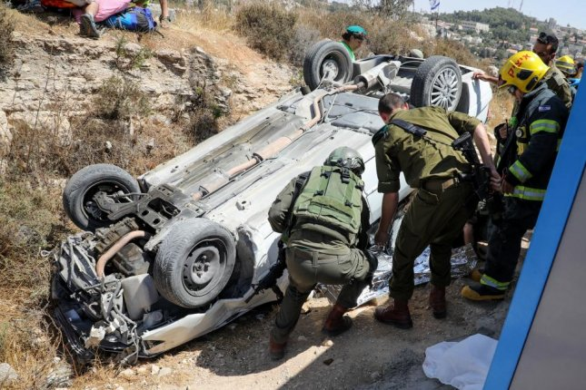 Israeli soldiers inspect a car authorities say rammed two people Friday in the West Bank settlement of Elazar. Photo by Gershon Elinson/EPA-EFE
