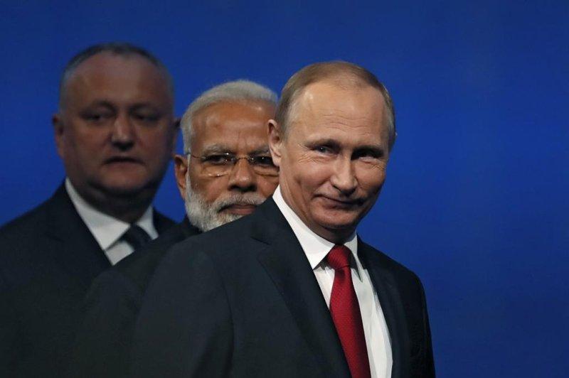 Russian President Vladimir Putin (R), Indian Prime Minister Narendra Modi (C) and Moldovan President Igor Dodon (L) enter a hall for a session of the St. Petersburg International Economic Forum on Friday. File Photo by Yuri Kochetkov/EPA