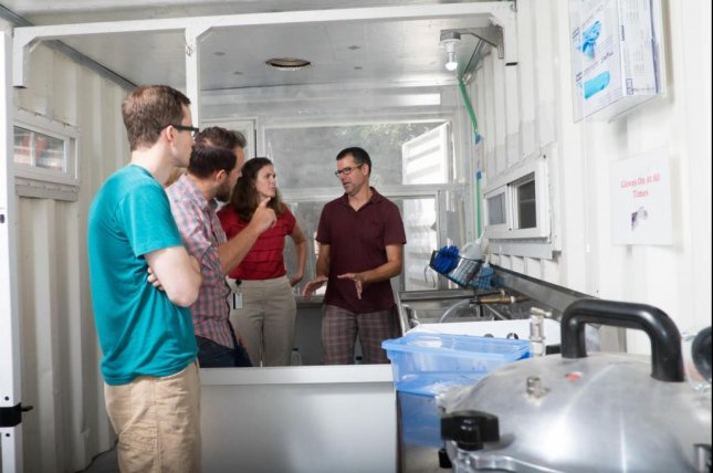 Rice University professors Maria Oden, second from right, and Douglas Schuler, right, give visitors a tour of the Sterile Box prototype. The unit was designed to sterilize and process surgical instruments in low-resource settings. Photo by Jeff Fitlow/Rice University