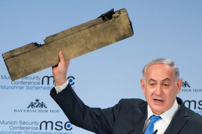 At a security conference Sunday, Israeli Prime Minister Benjamin Netanyahu shows a part of what he said was an Iranian drone missile shot down by the Israel Air Force this month. He made no mention of the arrests of seven associates in an influence-trading case in Israel. Photo by MSC/Preiss/EPA-EFE