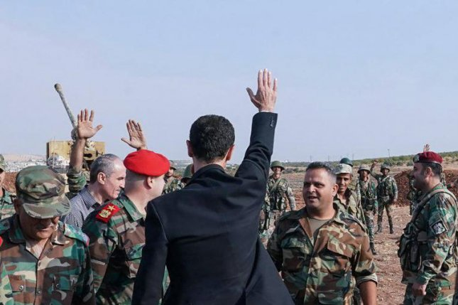 Syrian President Bashar al-Assad (C) meets with Syrian army personnel on frontlines of al-Habit town in Idleb countryside, Syria on Oct. 22. Syrian and Turkish forces fought against each other for the first time in northern Syria since a new Turkey offensive started. Photo by the Syrian Arab News Agency/EPA-EFE