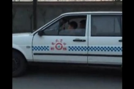 A young boy drives while his adult passenger focuses on a cellphone. Newsflare video screenshot