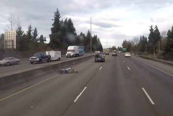 A motorcyclist sits on the trunk of a car after crashing at a high rate of speed on Interstate 5 in Washington. Screenshot: Life of Brian/YouTube