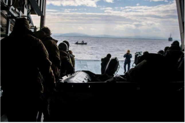 Sailors deployed with Mine Countermeasures Squadron 7 and members of the Japan Maritime Self-Defense Force move a combat rubber raiding craft aboard the minesweeper tender JS Uraga during Mine Warfare Exercise 1JA 2021. Photo by Mass Communications Specialist 2nd Class Nick Bauer/U.S. Navy