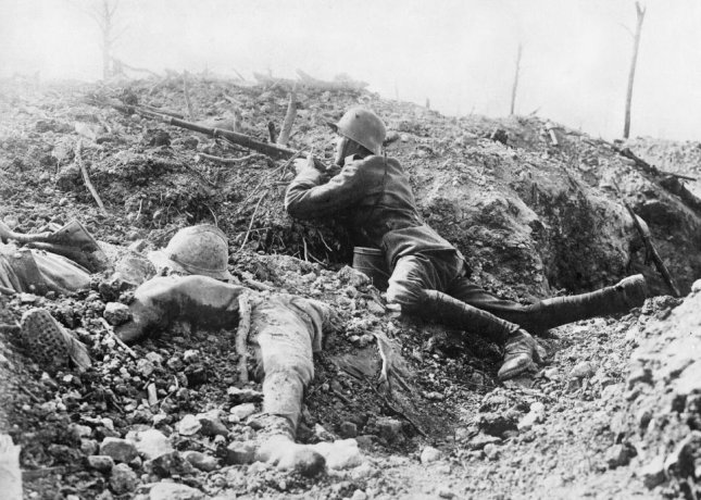 A German soldier aims his rifle from a shallow trench with the remains of a French soldier on his left near Fort Vaux outside Verdun, France. The Battle of Verdun lasted nearly a year and killed more than 300,000 soldiers, wounding more than 1 million. Geiser Theodore (Mons) Collection/IWM/UPI