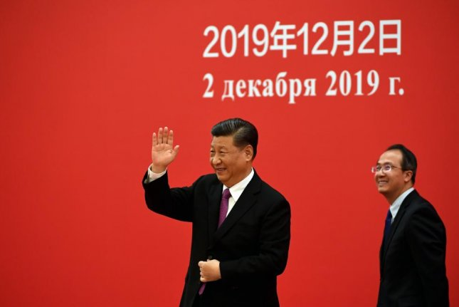 China's President Xi Jinping waves to Russian President Vladimir Putin via a video link from the Great Hall of the People in Beijing on Monday. Photo by Noel Celis/EPA-EFE