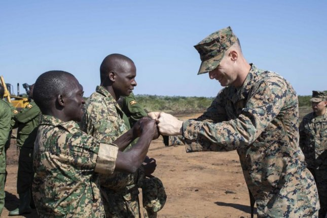 U.S. Marines and U.S. Navy Sailors with Special Purpose Marine Air-Ground Task Force, Crisis Response-Africa 20.1, Marine Forces Europe and Africa, and members of the Uganda People's Defense Force celebrate in Camp Singo, Uganda, in February. Photo by Grace Jenkins/U.S. Marines