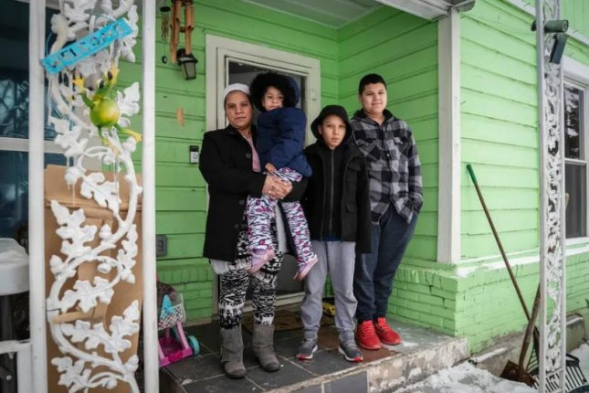 Marleny Almendarez, 38, with her niece Madelyne Hernandez, 3, and two boys, Aaron Hall, 11, and Matthew Hall, 14, stand outside their home in Dallas on Thursday. The family spent two nights at a mobile warming station to avoid the cold temperatures. Photo by Ben Torres for The Texas Tribune