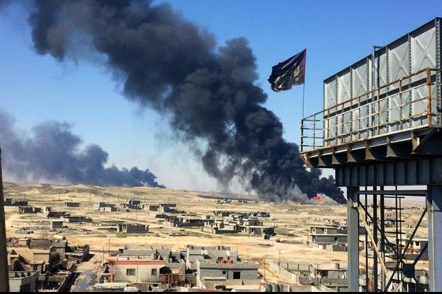 Smoke rises above Qayyarah displacement camp in March. Photo by Anna Lekas Miller/Refugees Deeply