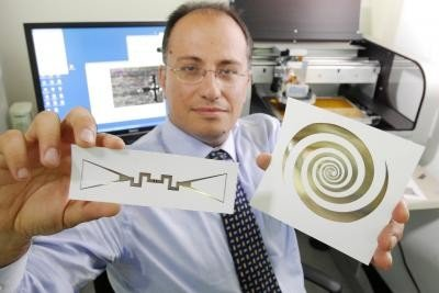 Georgia Tech School of Electrical and Computer Engineering professor Manos Tentzeris holds a sensor (left) and an ultra-broadband spiral antenna for wearable energy-scavenging applications. Both were printed on paper using inkjet technology. Credit: Georgia Tech Photo: Gary Meek
