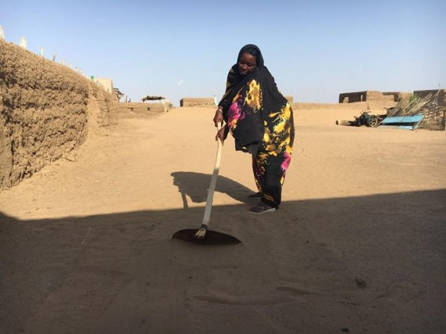 El Toma Abdel Maruf sweeps sand from outside her home in El Shababit, where the desert is creeping in due to climate change. Photo by Hannah McNeish/Women & Girls