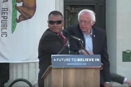 A Secret Service agent jumped onstage during Democratic presidential candidate Sen. Bernie Sanders' rally in Oakland, Calif., on Monday. Animal rights demonstrators hopped a bike rack barricade and tried rushing the stage. No injuries were reported. Screen shot courtesy ABC News/YouTube