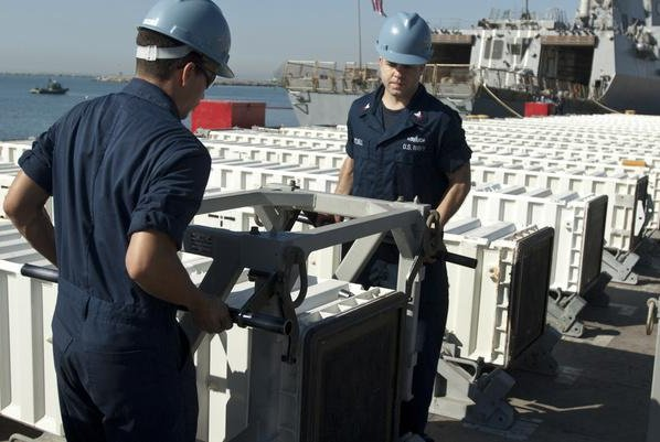 Missile canisters for the MK 41 Vertical launching System are loaded onto a ship. Photo courtesy BAE Systems
