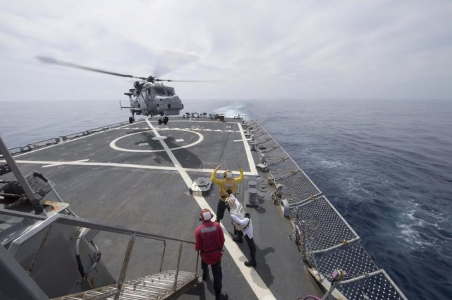 Boatswain's Mate 3rd Class Jake Ellingson signals to a British Royal Navy AW159 Wildcat helicopter during flight operations aboard the USS Ross in the Mediterranean Sea on March 23. Photo by Mass Communication Spec. 2nd Class Krystina Coffey/U.S. Navy