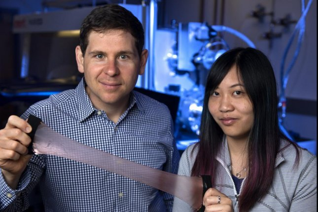 Alon Gorodetsky, UCI associate professor of chemical and biomolecular engineering, and Erica Leung, a UCI graduate student in the department, stretch out their new smart material, inspired by squid skin. Photo by Steve Zylius/UCI
