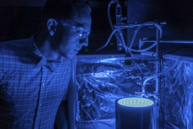 Researcher Fernando Uribe-Romo subjects his new synthetic material to artificial blue light, which it absorbs and uses to trigger a photosynthesis-like chemical reaction. Photo by the University of Central Florida